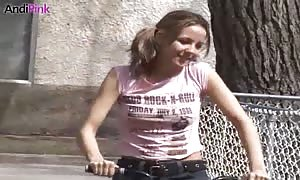 Andi Pink is riding on a bike and after which slowly beginning to undress